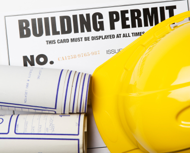 photo of building permit and construction hard hat